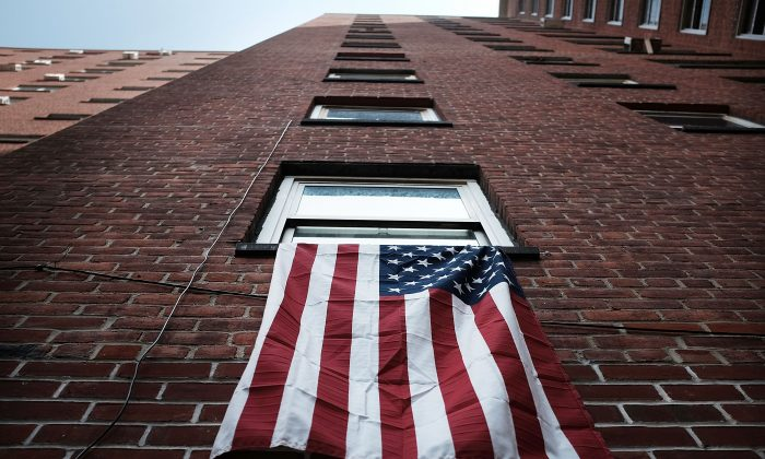 An American flag hangs from a window in an East Harlem public housing complex in New York City on May 19, 2015. (Spencer Platt/Getty Images)