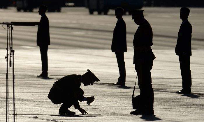 A Chinese soldier marks a spot on the ground before a military parade at Tiananmen Square in Beijing on Sept. 3, 2015. On Dec. 29, the 27th Army Group in Beijing, a unit notorious for partaking in the Tiananmen Square massacre on June 4, 1989, was disbanded, reorganized, and relocated to Shandong, a neighboring province. An army-wide reorganization is currently underway. (Wang Zhao/AFP/Getty Images)