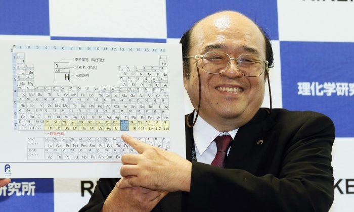 Kosuke Morita of Riken Nishina Center for Accelerator-Based Science points at periodic table of the elements during a press conference in Wako, Saitama prefecture, near Tokyo Thursday, Dec. 31, 2015.  (Kyodo News via AP)