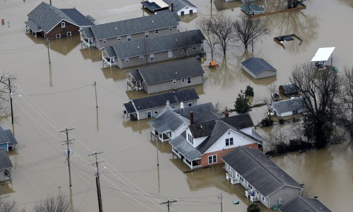 In this aerial photo, homes are surrounded by floodwater, Wednesday, Dec. 30, 2015, in Pacific, Mo. (AP Photo/Jeff Roberson)