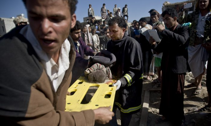 In this Thursday, March 26, 2015 file photo, people carry the body of a child they uncovered from under the rubble of houses destroyed by Saudi airstrikes near Sanaa Airport, Yemen. (AP Photo/Hani Mohammed)