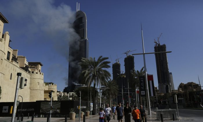A fire burns in the Address Downtown skyscraper in Dubai, United Arab Emirates on Friday, Jan. 1, 2016. The blaze began Thursday night before Dubai's annual New Year's Eve fireworks show at the Burj Khalifa, the world's tallest building which sits nearby. (AP Photo/Sunday Alamba)