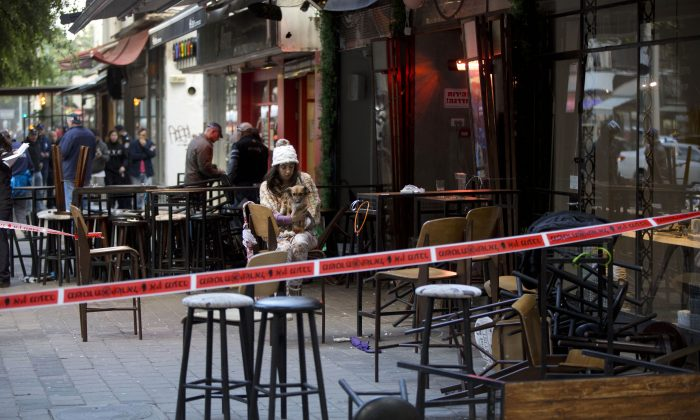 An Israeli eye witness sits with her dog at the scene of a shooting attack in Tel Aviv, Israel, Friday, Jan. 1, 2016. A gunman opened fire at a popular bar in the central Israeli city of Tel Aviv on Friday afternoon, killing two and wounding at least three others before fleeing the scene, police said. (AP Photo/Oded Balilty)