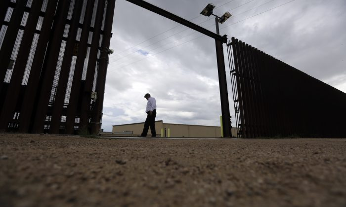 In this Sept. 15, 2015, photo, Othal Brand Jr., general manager of Hidalgo County Water Improvement District, walks along a gate in the border fence that run along the water plant, in Hidalgo, Texas. While 1,254 miles of border occur in Texas, the state has only about 100 miles of wall.  (AP Photo/Eric Gay)