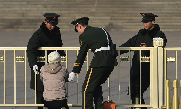Paramilitary police officers stop a woman as she protests on her knees in front of the Great Hall of the People in Beijing on March 13, 2015.  (GREG BAKER/AFP/Getty Images)