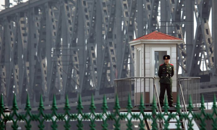 A Chinese border guard standing on a look out post by the bridge that crosses the Yalu river to the North Korean town of Sinuiju across from the city of Dandong on April 6, 2013. (STR/AFP/Getty Images)