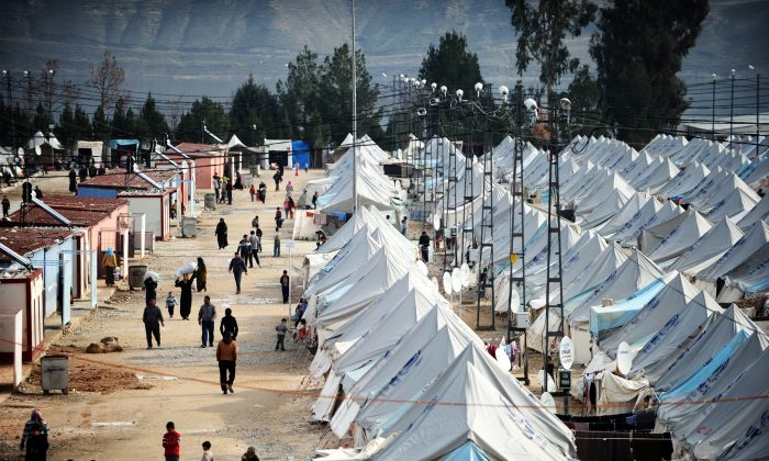 Syrian refugees walk among tents at Karkamis' refugee camp near the town of Gaziantep, south of Turkey, on on Jan. 16, 2014. (Ozan Kose/AFP/Getty Images)