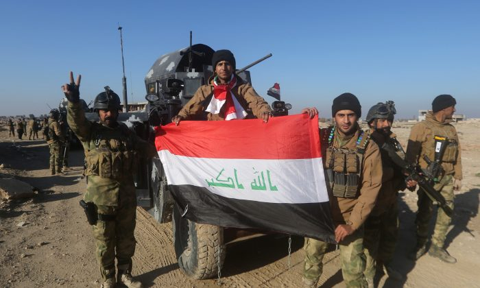 Members of Iraq's elite counterterrorism service pose with their national flag on Dec. 29, 2015, in the city of Ramadi, the capital of Iraq's Anbar Province, after Iraqi forces recaptured it from the Islamic State. (Ahmad al-Rubaye/AFP/Getty Images)