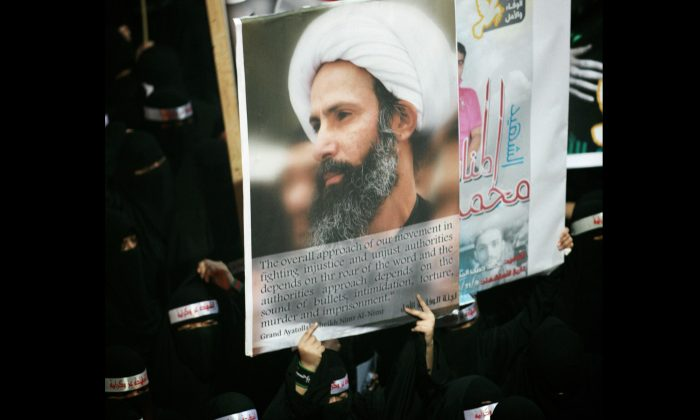 A Saudi anti-government protester carries a poster with the image of jailed Shiite cleric Sheik Nimr al-Nimr during the funeral of three Shiite Muslims allegedly killed by Saudi security forces in the eastern town of al-Awamiya, Saudi Arabia, on Sept. 30, 2012. Saudi Arabia says it has executed 47 prisoners, including leading Shiite cleric Sheikh Nimr al-Nimr. The cleric's name was among a list of the 47 prisoners executed carried by the state-run Saudi Press Agency. It cited the Interior Ministry for the information. (AP Photo)