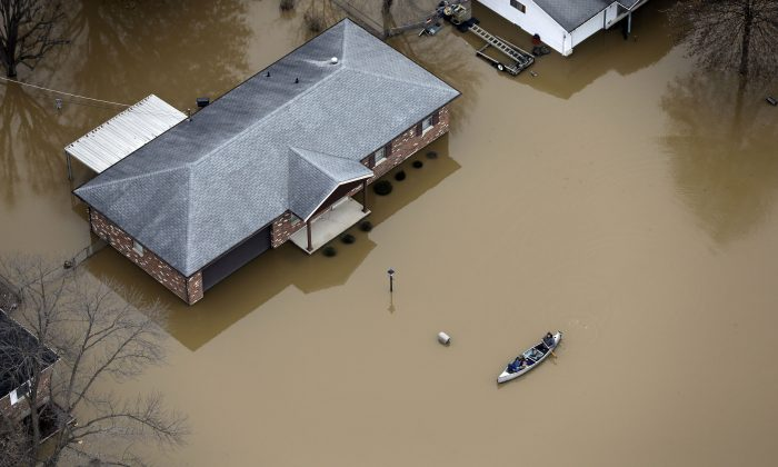 In this aerial photo, people use a canoe to navigate a flooded street in Arnold, Mo., on Dec. 31, 2015. Surging Midwestern rivers forced hundreds of evacuations, threatened dozens of levees and brought transportation by car, boat or train to a virtual standstill Thursday in the St. Louis area. (AP Photo/Jeff Roberson)