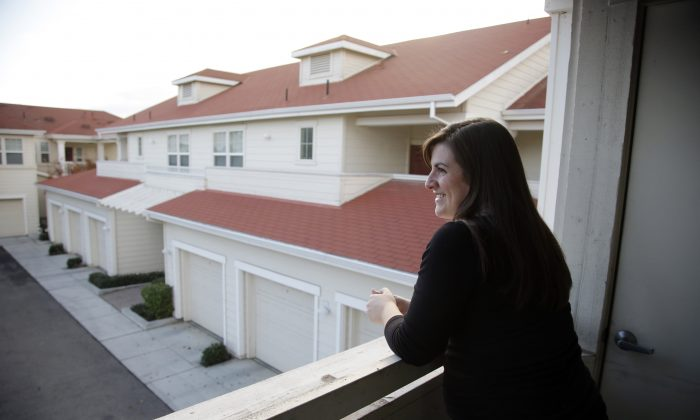 Katy Howser, a kindergarten teacher in the Santa Clara School District, looks out from the balcony of her apartment at Casa Del Maestro, an apartment complex for teachers, in Santa Clara, Calif., Dec. 11, 2015. School districts in high cost-of-living areas and rural communities that have long struggled to staff classrooms are considering buying or building rent-subsidized apartments as a way to attract and retain teachers amid concerns of a looming shortage. (AP Photo/Marcio Jose Sanchez)