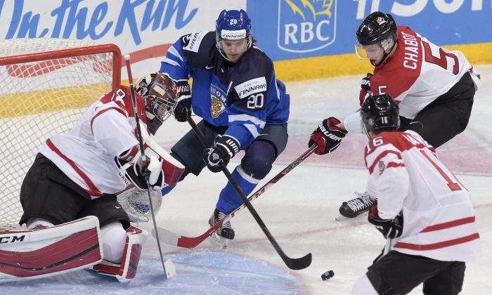 Finland's Sebastian Aho goes for a loose puck against Canada's goalie Mackenzie Blackwood, MitchMarner, and Thomas Chabot at the 2016 IIHF World Junior Ice Hockey Championships quarterfinal in Helsinki, Finland on Jan. 2, 2016. (Markku Ulander/Lehtikuva via AP)
