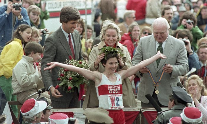 FILE - In this April 19, 1983, file photo, Joan Benoit receives her laurel wreath and reacts to cheering crowds after winning the Boston Marathon in record time for the women's division, in Boston. Massachusetts Lt. Gov. John Kerry (L) in red tie, stands behind her. (AP Photo/File)