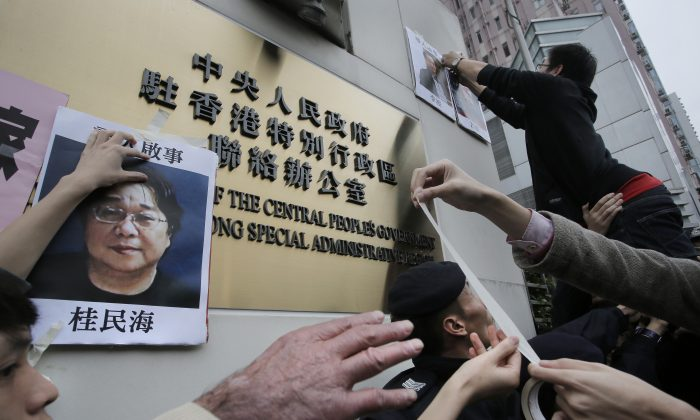Protesters try to stick photos of missing booksellers during a protest outside the Liaison of the Central People's Government in Hong Kong on Jan. 3, 2016. (AP Photo/Vincent Yu)