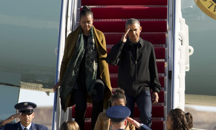 President Barack Obama, first lady Michelle Obama, and their daughters Sasha and Malia arrive from vacation in Hawaii at Andrews Air Force Base, Md., on Jan. 3, 2016. (AP Photo/Jose Luis Magana)