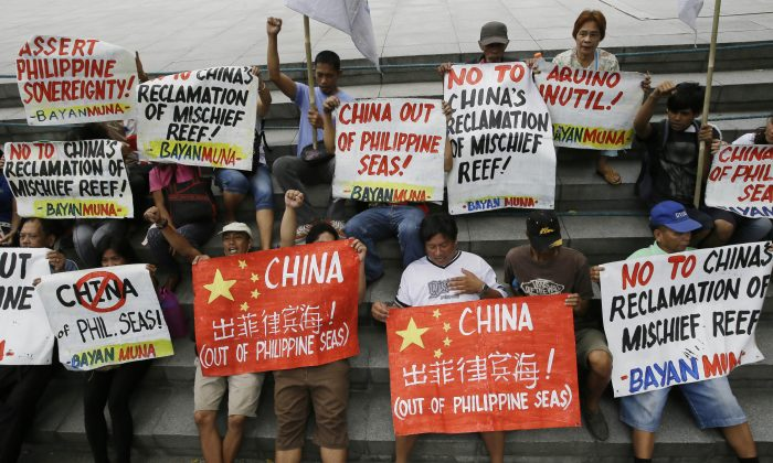 """Protesters display placards during a rally at the Chinese Consulate at the financial district of Makati city, east of Manila, Philippines, on April 17, 2015, to protest moves by China in """"fortifying"""" its claims at the disputed Spratlys Islands in the South China Sea. China's campaign of island building in the South China Sea might soon quadruple the number of airstrips available to the People's Liberation Army in the highly contested and strategically vital region. That could be bad news for other regional contenders, especially the U.S., the Philippines, and Vietnam. (AP Photo/Bullit Marquez)"""