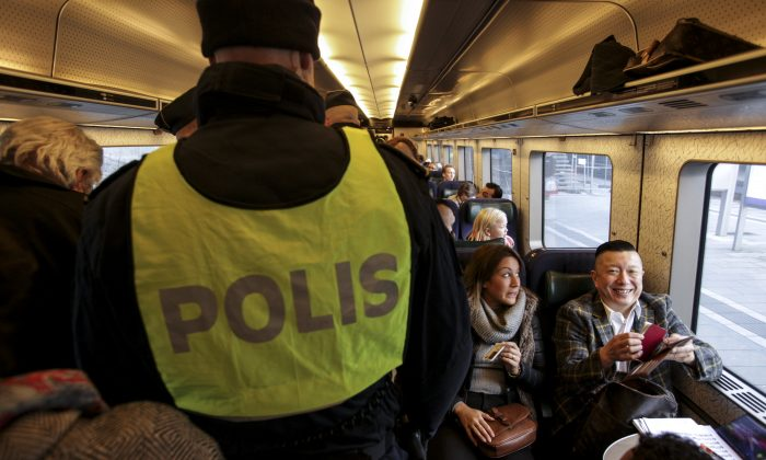 Swedish police officers on the train from Copenhagen in Malmo, Sweden, on Nov. 12, 2015. (Stig Ake Jonsson/TT via AP)