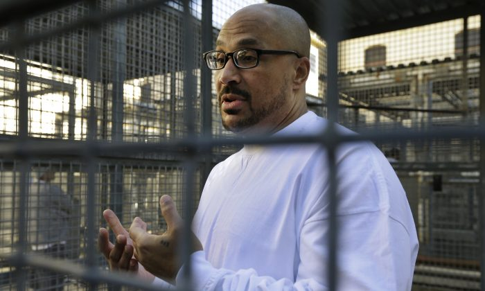 In this photo taken on Tuesday, Dec. 29, 2015, inmate Charles Crawford gestures while speaking to reporters in a recreation yard at San Quentin State Prison in San Quentin, Calif. (AP Photo/Ben Margot)