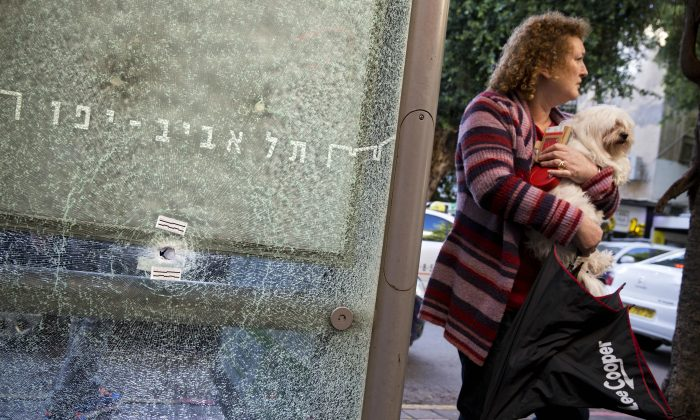 An Israeli woman holds her dog next to a bus station shattered by bullets at the scene of a deadly shooting attack, in Tel Aviv, Israel, on Jan. 2, 2016. For all its years of strife, Israel has rarely seen anything quite like this: an armed, wanted Arab killer on the loose who is spreading fear across the land. Even the proudly stoic are keeping children home from school as they brace for another potential attack after the weekend's deadly daytime shooting at a Tel Aviv bar in what has become the most baffling event in a three-month wave of violence. (AP Photo/Oded Balilty)
