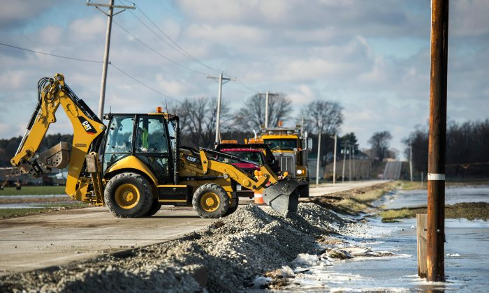 Tazewell County Highway Department work crews add gravel to rebuild the shoulder of Townline Road as floodwater from the Mackinaw River start to recede in Illinois on Jan. 4, 2016. (Fred Zwicky/Journal Star via AP)