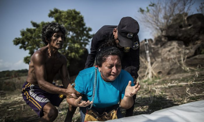 The sister of Alberto Hernández Escalante mourns over the body of her brother, found in a clandestine grave, in a rural area near Caserio el Chumpe, El Salvador, on May 28, 2015. In a report released Monday, Jan. 4, 2016, authorities said that killings spiked by nearly 70 percent in El Salvador in 2015, resulting in a sky-high homicide rate that could make it the world's most violent nation. (AP Photo/Manu Brabo)