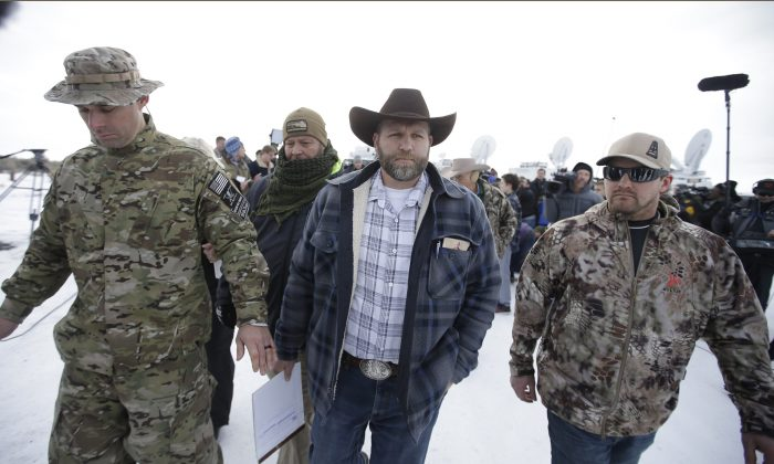 Ammon Bundy, center, one of the sons of Nevada rancher Cliven Bundy, walks off after speaking with reporters during a news conference at Malheur National Wildlife Refuge headquarters Monday, Jan. 4, 2016, near Burns, Ore. Bundy, who was involved in a 2014 standoff with the government over grazing rights told reporters on Monday that two local ranchers who face long prison sentences for setting fire to land have been treated unfairly. (AP Photo/Rick Bowmer)