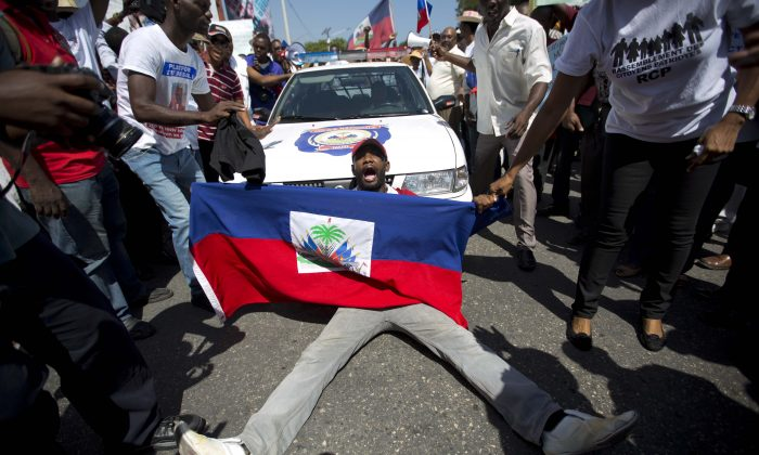 "A demonstrator holding a Haitian flag shouts, ""No racism"" as he blocks a police car during a march to the prime minister's office to protest the Dominican Republic's deportation of Haitians, in Port-au-Prince, Haiti, on July 21, 2015. A Dominican court said people born to non-citizens were not automatically entitled to citizenship. The decision was extended back to 1929, retroactively stripping people of the right they believed they had since birth. (AP Photo/Dieu Nalio Chery)"