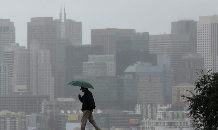 Richard Polich crosses a street in the rain on Tuesday, Jan. 5, 2016, in San Francisco. (AP Photo/Jeff Chiu)