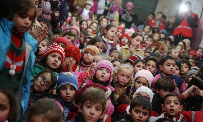 Syrian children attend an event organised by the Syrian Arab Red Crescent for New Year's eve celebrations in a rebel-controlled area of Arbeen, on the outskirts of the capital Damascus, on Dec. 31, 2015. (Abd Doumany/AFP/Getty Images)