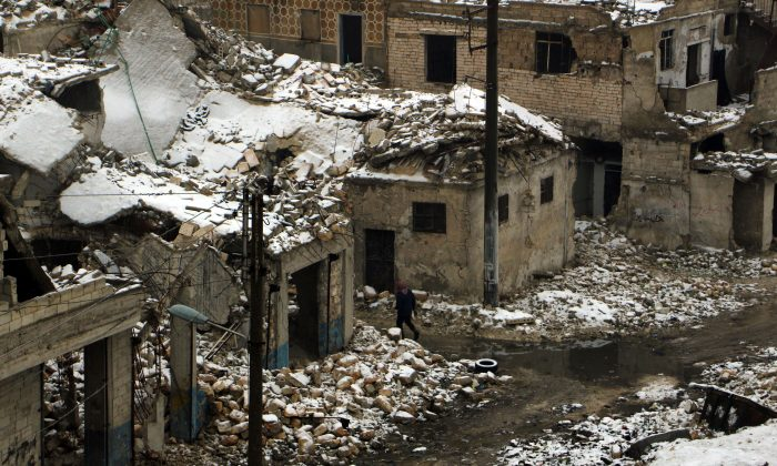 A Syrian man walks past damaged houses following a snow storm in the northern Syrian city of Aleppo on Jan. 5, 2016. The conflict in Syria has killed more than 250,000 people and forced about 11 millions to flee their homes since it broke out in March 2011. (Karam al-Masri/AFP/Getty Images)