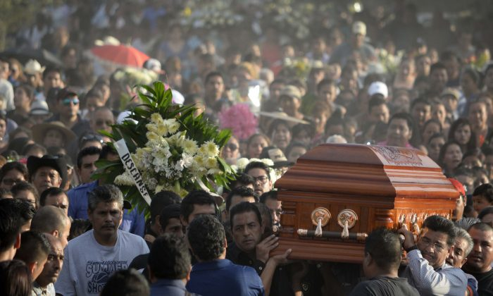 Mourners carry the coffin of slain mayor of Temixco, Gisela Mota, to the cemetery in Pueblo Viejo, Mexico, on Jan. 3, 2016. Mota took office as mayor of the city of on Jan. 1 and was shot at her home on Jan. 2. The governor of the southern Mexican state of Morelos says the killing of the mayor was a warning by drug gangs, meant to convince other officials to reject state police control of local forces. (AP Photo/Tony Rivera)