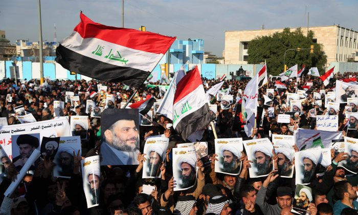 Followers of Shiite cleric Muqtada al-Sadr chant anti-Saudi government slogans and wave national flags as they hold posters of Sheikh Nimr al-Nimr and Shiite cleric Muqtada al-Sadr during a demonstration in Baghdad, Iraq, on Jan. 4, 2016. (AP Photo/Khalid Mohammed)