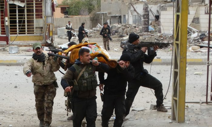Iraqi security forces and allied Sunni tribal fighters evacuate an injured woman after she was shot by Islamic State fighters as she tried to cross from neighborhoods under control of ISIS to neighborhoods under control of Iraqi security forces in Ramadi, 70 miles (115 kilometers) west of Baghdad, Iraq, on Jan. 4, 2016. Iran is a key ally of the Shiite-led government in Baghdad, has helped it in the fight against the Islamic State group and supports powerful Shiite militias in the country. But at the same time, Baghdad is trying to rebuild long strained ties with Saudi Arabia–which only last week sent an ambassador to Baghdad for the first time in 25 years. (AP Photo)