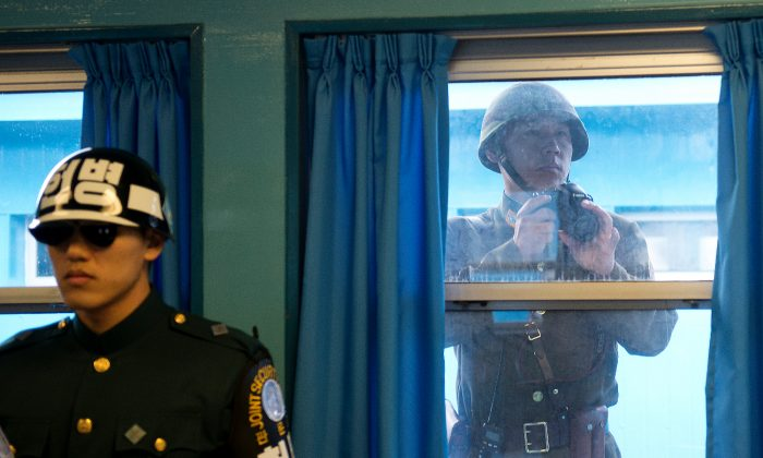 A North Korean Soldier takes photos through the window while U.S. Army Gen Martin E. Dempsey, chairman of the Joint Chiefs of Staff, is briefed at the demilitarized zone in South Korea on Nov. 11, 2012. (D. Myles Cullen/Department of Defense)
