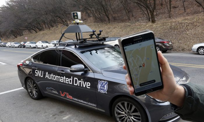 A researcher fromm the Intelligent Vehicle IT Research Center at Seoul National University shows the smartphone application for the driverless car called Snuber with a fixture on its roof with devices that scan road conditions at Seoul National University's campus in Seoul, South Korea, Tuesday, Jan. 5, 2016. (AP Photo/Lee Jin-man)