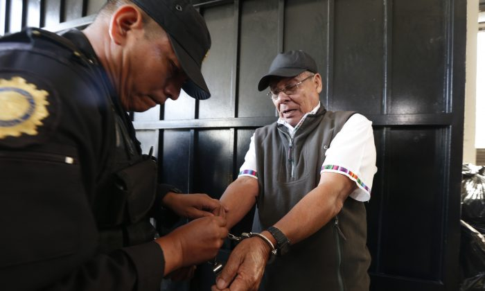 A police officer removes handcuffs from Benedicto Lucas Garcia, a former army commander credited with founding Guatemala's paramilitary groups, before escorting Lucas Garcia into a courtroom in Guatemala City on Jan. 6, 2016. On Wednesday, prosecutors arrested Lucas Garcia, the brother of deceased former President Fernando Romeo Lucas Garcia in connection with killings and disappearances during the country's 1960–1996 civil war. (AP Photo/Moises Castillo)