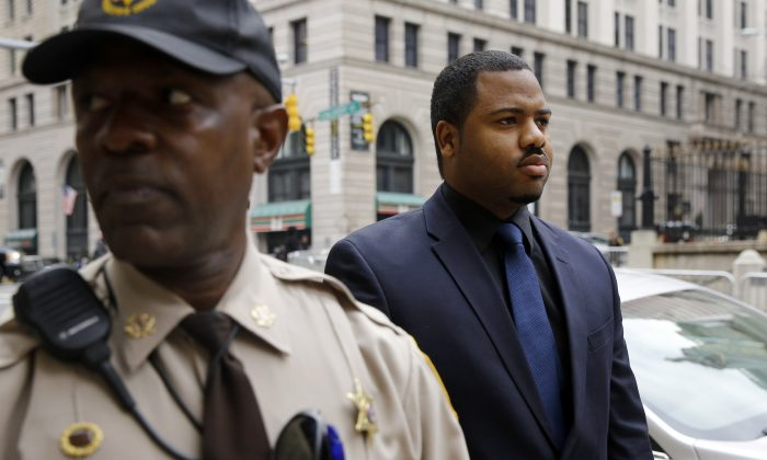Officer William Porter, right, one of six Baltimore city police officers charged in connection to the death of Freddie Gray, walks into a courthouse during jury deliberations, Wednesday, Dec. 16, 2015, in Baltimore. (AP Photo/Patrick Semansky)