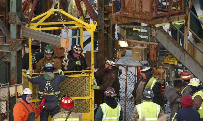 The fourth group of workers emerge from an elevator on Jan. 7, 2016, after they were stuck overnight in a shaft at the Cayuga Salt Mine in Lansing, N.Y. (Simon Wheeler/The Ithaca Journal via AP, Pool)