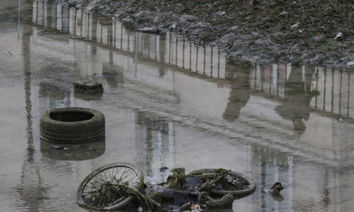 A bicycle and a tire lay on the ground of the canal Saint-Martin as the canal is drained for maintenance in Paris, Wednesday, Jan. 6,  2016. Paris' Canal Saint-Martin will be drained this week for cleaning, first into a puddle then when the final underwater creatures have been moved to safety into a dry ditch. The canal, popular with Parisians and visitors alike for its arched bridges, locks and trendy surrounding neighborhood, will be emptied for the first time in 14 years. (AP Photo/Michel Euler)