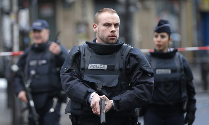 Police officers secure the perimeter near the scene of a fatal shooting which took place at a police station in Paris on Jan. 7, 2016. (AP Photo/Christophe Ena)