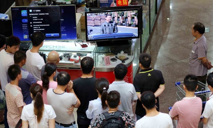 People gather in front of a television east China's Fujian Province on Sept. 3, 2015. (STR/AFP/Getty Images)