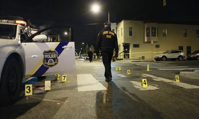 An investigator walks through the scene of a shooting Friday, Jan. 8, 2016, in Philadelphia. A Philadelphia police officer was shot multiple times by a man who ambushed him as he sat in his marked police cruiser, authorities said. (AP Photo/Joseph Kaczmarek)