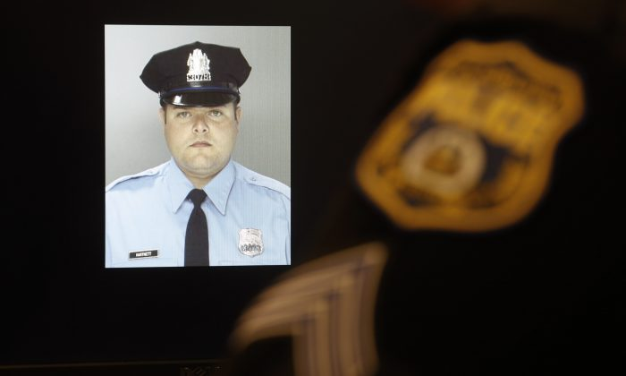 An officer sits next to a displayed image of Officer Jessie Hartnett ahead of a news conference Friday, Jan. 8, 2016, in Philadelphia. (AP Photo/Matt Rourke)