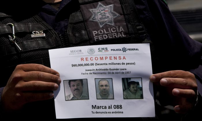"""In this July 16, 2015 file photo, a Federal Police shows a reward notice for information leading to the capture of drug lord Joaquin """"El Chapo"""" Guzman, who made his escape from the Altiplano maximum security prison via an underground tunnel, in Almoloya, west of Mexico City. (AP Photo/Marco Ugarte)"""