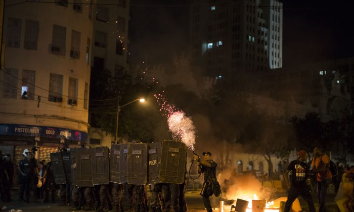 A police officer fires tear gas toward protesters during a march against bus fare hikes in Rio de Janeiro, Brazil, on Jan. 8, 2016. The march, which is also taking place in other Brazilian capitals, began peacefully in downtown Rio de Janeiro but turned violent. (AP Photo/Felipe Dana)