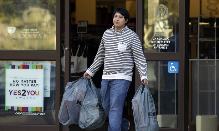 A man carries bags out of a department store, in Alameda, Calif., on Dec. 17, 2015. U.S. consumer spending rebounded in November after a weak showing in October, while a key inflation gauge posted the fastest year-over-year increase in 11 months. The Commerce Department said Wednesday, Dec. 23, that consumer spending increased 0.3 percent in November after an essentially flat reading in October and a 0.2 percent gain in September. Personal income rose a solid 0.3 percent in November, reflecting solid gains in wages and salaries, after a 0.4 percent October increase. (AP Photo/Ben Margot)
