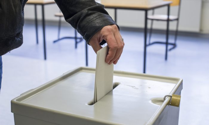 A voter puts his ballot in a ballot box at a primary school in Halle, Germany, on Sept. 22, 2013. (Jens Schlueter/Getty Images)