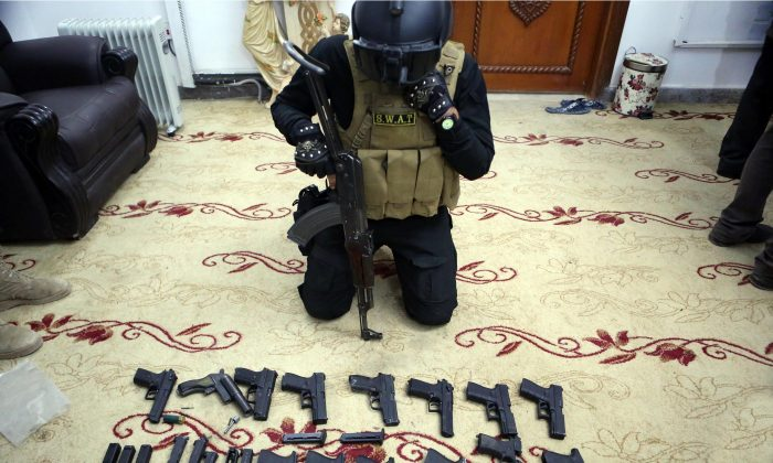 A policeman displayed weapons used by murderers and thieves, at police headquarters in Basra, 340 miles (550 kilometers) southeast of Baghdad, Iraq, on Dec. 19, 2015. Local officials blame the lack of security forces, many of them have been dispatched to front lines, for the soaring thefts, armed robberies, kidnapping for ransom, bloody tribal disputes and drug trafficking. Residents complain that political infighting over government posts and growing influence of Shiite militias have exacerbated the situation and weakened the role of the remaining security forces in the province. (AP Photo/Nabil al-Jurani)