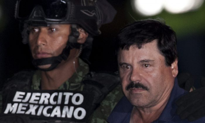 """Mexican drug lord Joaquin """"El Chapo"""" Guzman (R) is escorted by soldiers and marines to a waiting helicopter, at a federal hangar in Mexico City on Jan. 8, 2016. (AP Photo/Marco Ugarte)"""