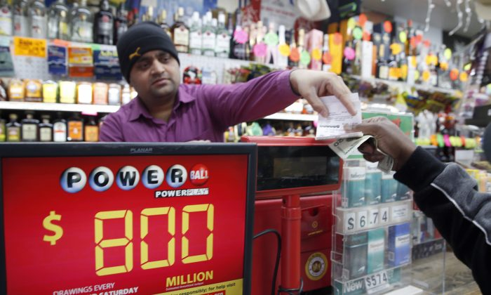 Jay Suthar sells Powerball tickets at Pine Liquors in Fort Washington, Md., on Jan. 8, 2016. With Powerball sales doubling previous records, the odds are growing that someone will win Saturday's $800 million jackpot, but if no one matches all the lottery numbers, next week's drawing is expected to soar past $1 billion. (AP Photo/Alex Brandon)
